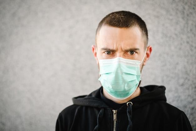 Коронавируса. человек, носящий маску для предотвращения инфекции на фоне серой стены, респираторного заболевания, такого как грипп, 2019-нков. эпидемия. берегите свое здоровье. концепция карантина. мерс-ков.