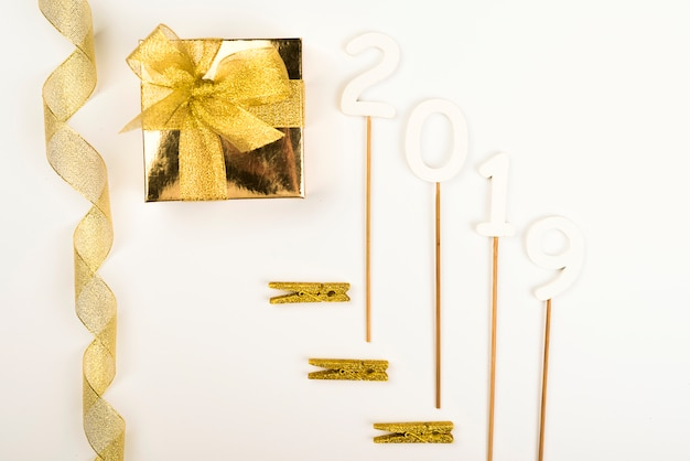 Золотые новогодние украшения 2019 года, лежащие в композиции