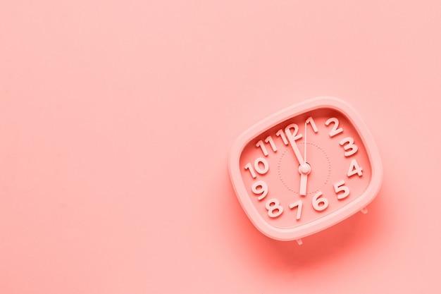 Розовый будильник лежа на желтой поверхностной предпосылке. модный живой коралловый цвет года 2019. вид сверху.