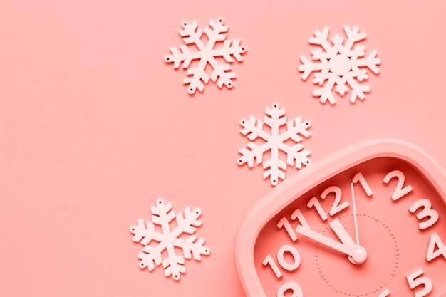 Розовый будильник с игрушками и снежинки, лежа на желтом фоне поверхности. новый год или рождество концепция. модный живой коралловый цвет года 2019. вид сверху. справиться с космосом.