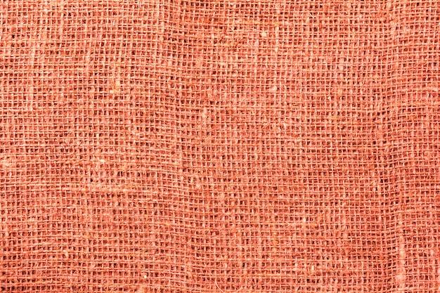 Мешковина, холст ткани текстуры фона. модный живой коралловый цвет 2019 года. ноль отходов концепции. вид сверху. копировать пространство