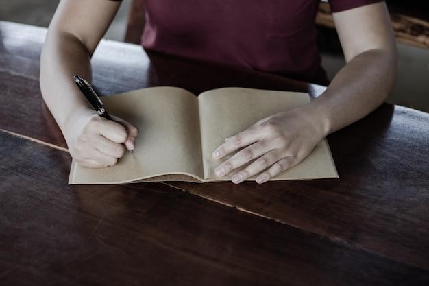 ペンを持つ手のクローズアップ、それは手紙作家のようです。仕事の創造的なアイデア2019年の目標、