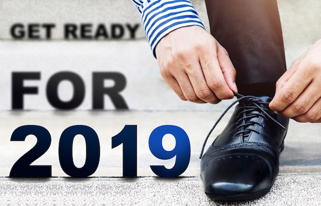 2019年の概念、屋外の階段のビジネスマンの靴紐