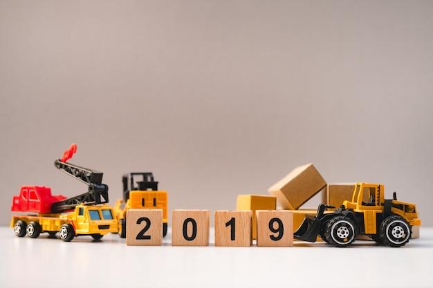 Деревянный блок год 2019 со строительным автомобилем и картонными коробками в качестве концепции логистики