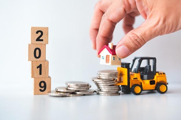 Рука движется миниатюрный дом на стеке монет с деревянным блоком год 2019