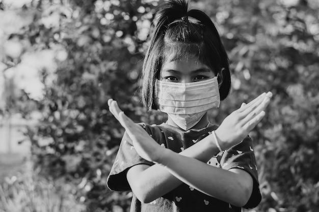 2019年コロナラウイルス病と戦うためにサージカルマスクを身に着けている女の子。