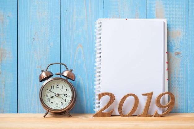 ノートブック、レトロな目覚まし時計、木製の数字が付いた2019年の新しい年