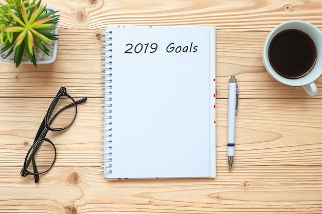 2019ノートブック、黒のコーヒーカップ、ペン、テーブル上の眼鏡でゴール