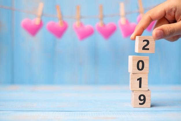 青いテーブル背景にピンクのハート形の装飾とテキストのコピースペース2019木製キューブ。ビジネス、決議、新年おめでとう、そして幸せなバレンタインデーの休日の概念