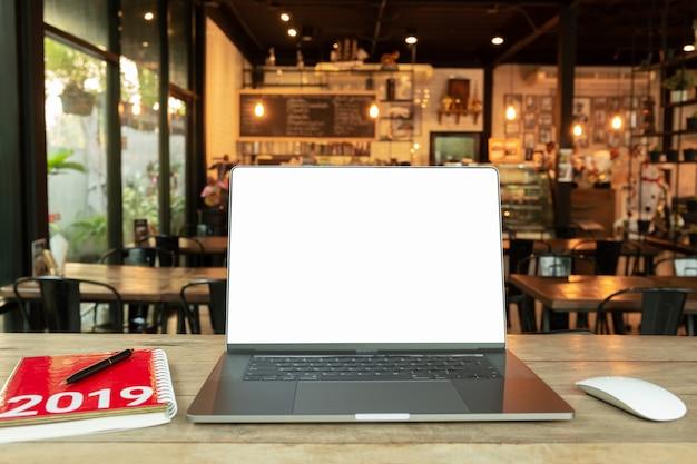 空白の画面を持つマウスとカフェの木製の机の上の2019年電卓とノートブックを持つノートパソコン。