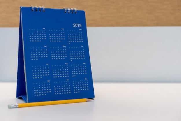 Закройте календарь синего цвета 2019, стоя на белом столе в офисе