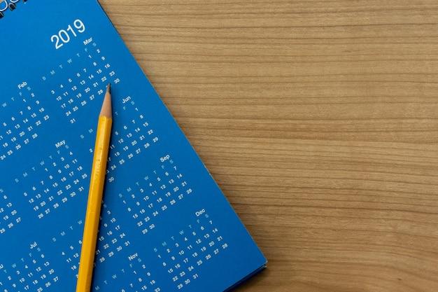 Желтый карандаш на синем графике календарного месяца 2019, чтобы назначить встречу