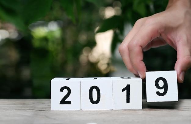 Вручите держать белый деревянный календарь кубов с номером 2019 с предпосылкой природы.