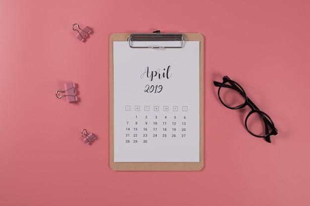 Плоский лежал календарь с буфера обмена и очки на розовом фоне. апрель 2019 года. вид сверху.