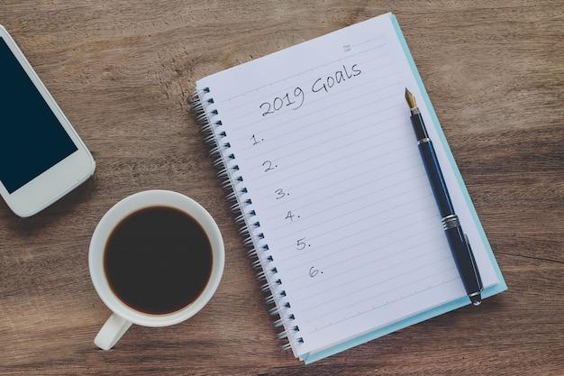 コーヒー、ペン、スマートフォンを備えたブックノートの2019年目標テキスト。