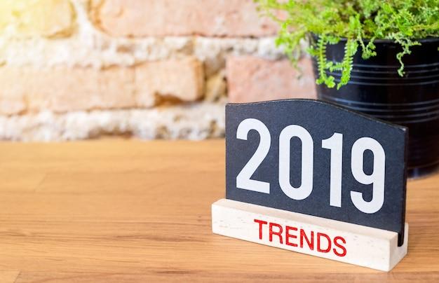 Новый год 2019 тенденции на доске знак и зеленый завод на деревянный стол на кирпичной стене