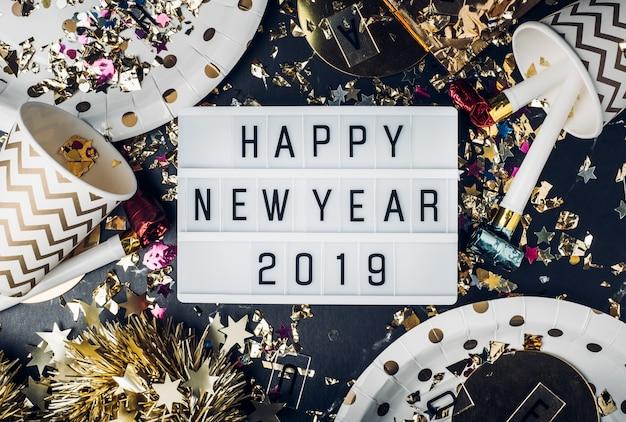 パーティーの杯、パーティーブロワー、はさみ、色とりどりのライトボックスで、新年あけましておめでとうございます2019