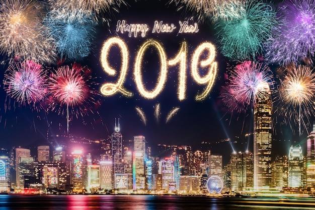 夜の時間のお祝いで街並みの建物の上に新年2019年の花火があります