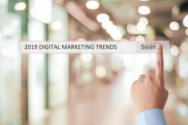 ぼかしのオフィスの背景の上の検索バーに2019年デジタルマーケティング動向に触れる男の手