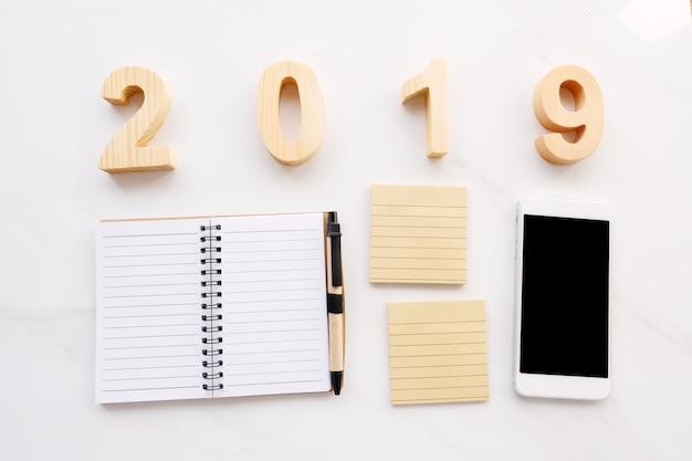 2019木製文字、白紙のメモ用紙、白い背景の上のスマートフォン