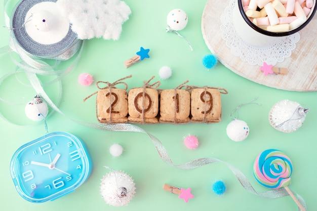 明るいパンチの色の上に祝賀クリスマスの冬の装飾とクッキーの数字2019