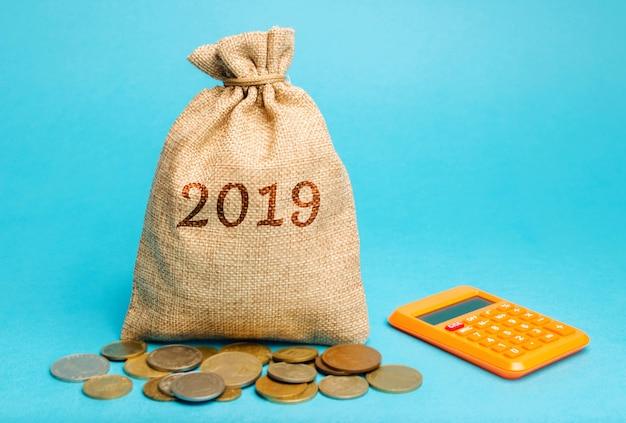 単語2019と電卓を備えたお金の袋。ビジネス財務レポート。