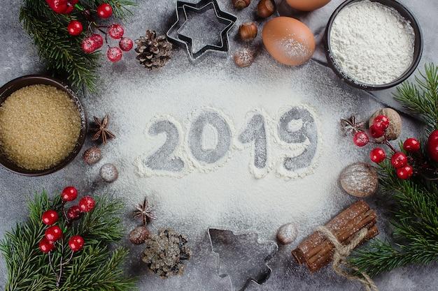 2019テーブルのベーカリーの材料とお祝いのクリスマスの装飾と小麦粉で作られたテキスト
