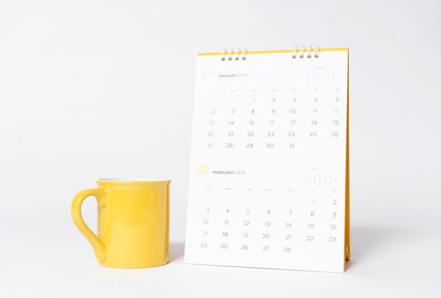 Пустой желтый колпачок макет и бумага спиральный календарный год 2019 на сером фоне.