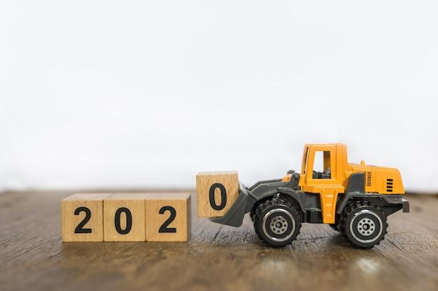 2020年の新年コンセプト。木製テーブルとコピースペースを持つ白い背景のおもちゃローダートラックマシン車ロードされた数0木製ブロックグッズのクローズアップ