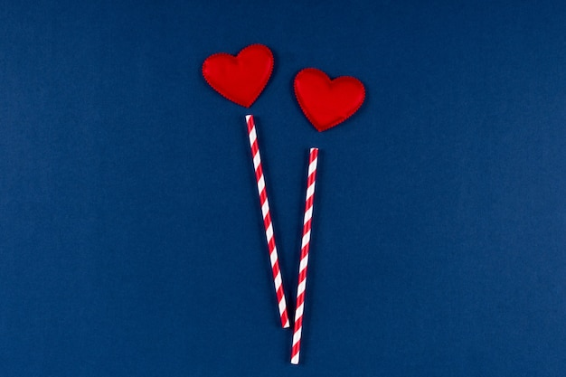 Красная бумажная солома с сердцем на классическом синем цветном фоне 2020 года. день святого валентина 14 февраля концепция. плоская планировка, копия пространства, вид сверху.