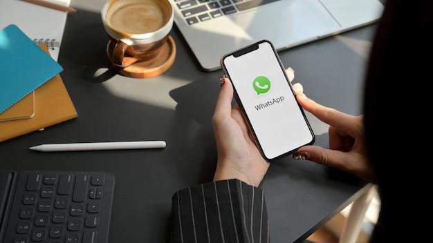 チェンマイ、タイ-2020年2月1日:whatsapp画面でiphoneを保持している女性。 whatsappはメッセージングアプリケーションです
