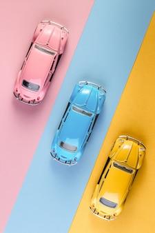 イジェフスク、ロシア、2020年2月15日。ピンク、黄色、青の背景に小さなビンテージレトロなおもちゃの車