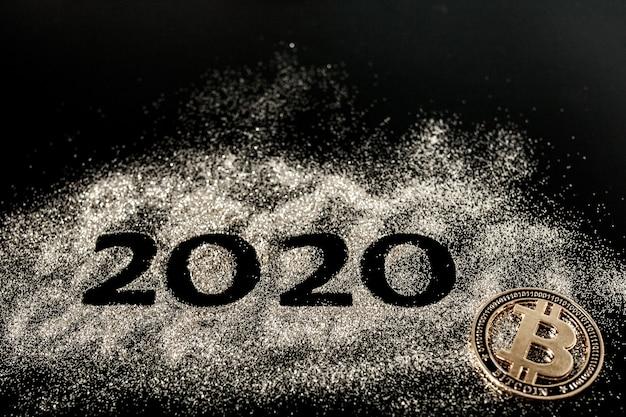 С новым годом 2020. творческий коллаж из чисел два и ноль составил 2020 год. красивый сверкающий золотой номер 2020 и биткойн на черном