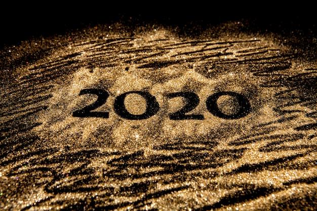С новым годом 2020. творческий коллаж из чисел два и ноль составил 2020 год. красивый сверкающий золотой номер 2020 на черном.