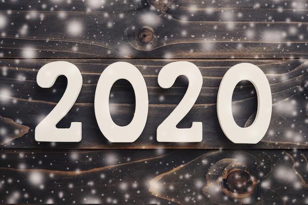 2020年の新年コンセプト:テーブルの背景に雪で2020年の木材数。