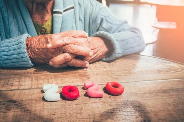 Старый человек руки, держа номер 2020 на деревянный стол. концепция: в 2020 году пожилое население мира резко возрастает.