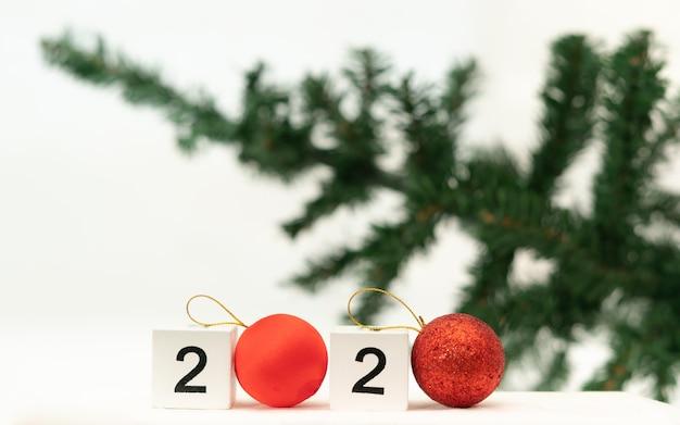 ぼやけたクリスマスツリーの背景で2020年の数字。 2020年のトレンドコンセプト。