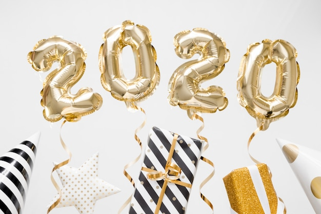 新年あけましておめでとうございます2020のお祝い。ギフトと白い背景の上の金箔風船数字2020