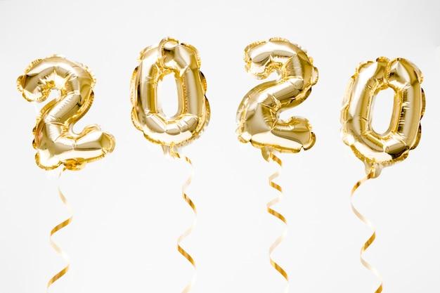 Празднование нового года 2020. золотая фольга шары цифра 2020 висит в воздухе на белом фоне