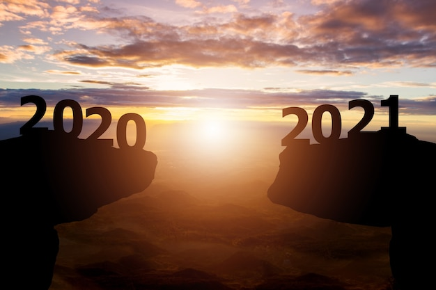 Between 2020 and 2021 years with silhouette sunset background