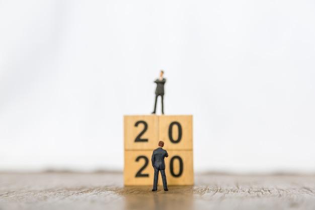 2020年と事業計画。ウッドナンバーブロックのスタックの前に立っている2つの実業家ミニチュアフィギュアのクローズアップ