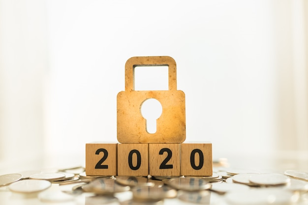 2020 business, planning, finance and money security concept. close up of wooden master key lock icon on wood number block on pile of coins with copy space.