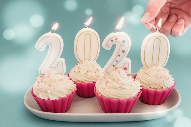 2020 candles on cupcakes with whip cream frosting using pink silicone reusable cups