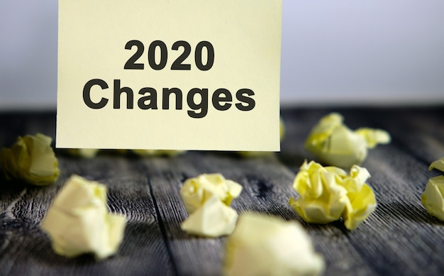 2020 changes text on a yellow sticker. written crumpled sheets with changes