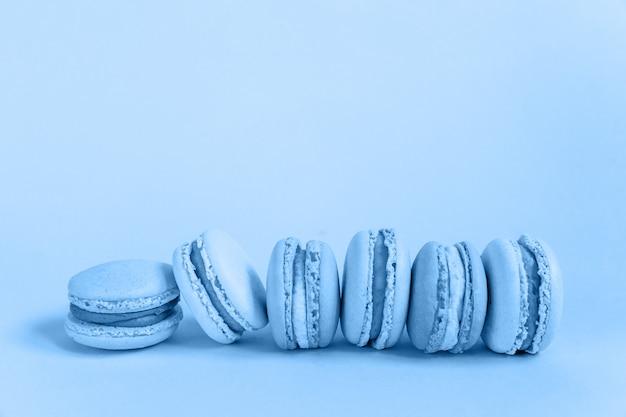 Сладкий миндальный торт макарон или миндальное печенье окрашены в модный цвет 2020 года classic blue, изолированных на синем фоне пастельных. макрос с использованием цвета. copyspace.