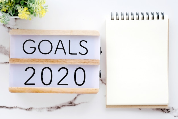 2020 goals on wood box and blank notebook paper on white marble background