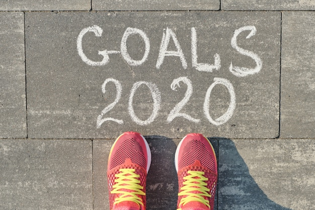 2020 goals, written on gray sidewalk with woman legs in sneakers