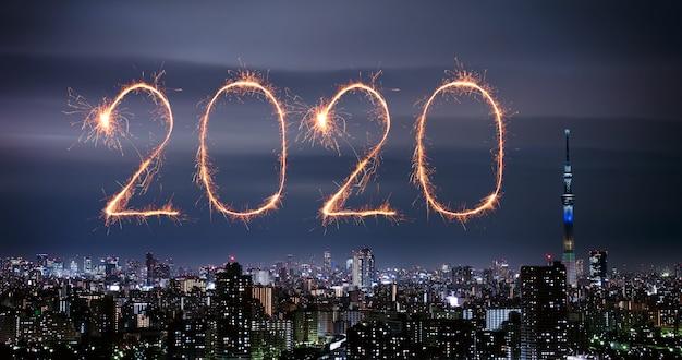 Фейерверк «счастливый новый год 2020» над ночным пейзажем токио, япония