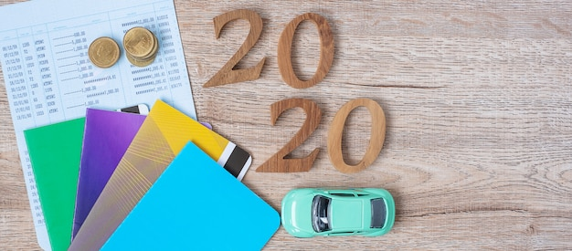 2020 happy new year with book bank and car on wood table