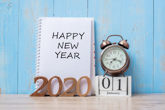 2020 happy new year  with notebook, retro alarm clock and wooden number.